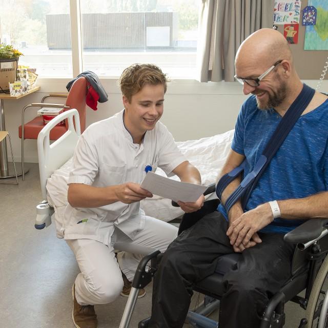 Een patiënt vult samen met een zorgverlener de vragenlijst in.